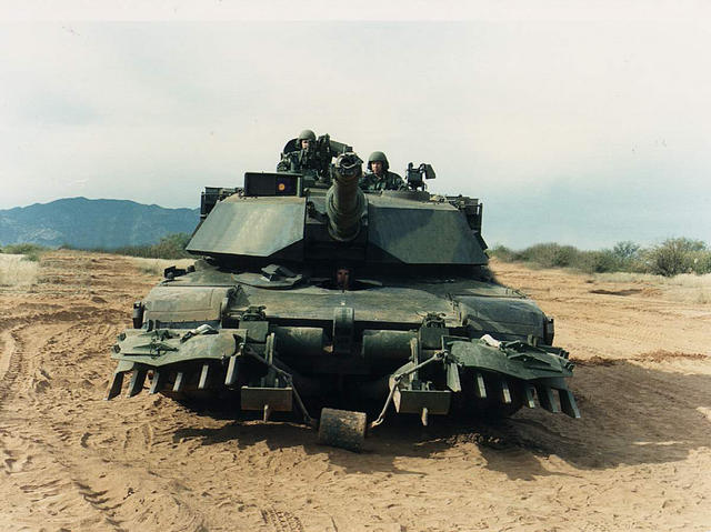 M1 Abrams tank with mine plow, in forest camo (front)
